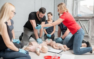 Young woman instructor helping to make first aid heart compressions with dummy during the group training indoors